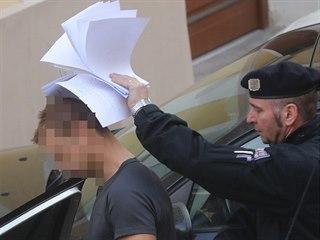 Policie odvádí od soudu do vazební věznice staršího z obviněných z vraždy...