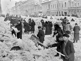 Obyvatelé odklízejí sníh a led v ulicích Leningradu za blokády města v zimě...