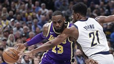 LeBron James (23) z LA Lakers najíždí kolem Thaddeuse Younga (21) z Indiany.