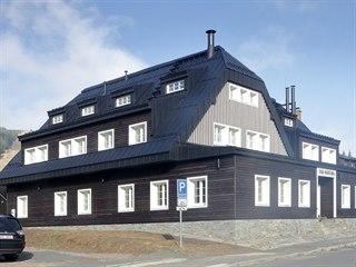 Původní část má fasádu z tradičního opalovaného dřeva.