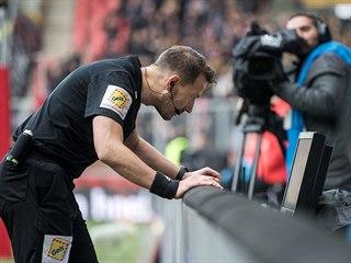 Rozhodčí Karel Hrubeš v derby mezi Slavií a Spartou zkoumá na videu penaltovou...