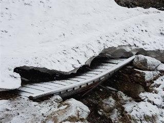 Dřevěný mostek u Trkače v Rudné rokli poškodil nápor sněhu, jeden z nosníků se...