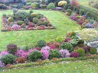 Opečovávaná okrasná část zahrady na podzim, plná barev.