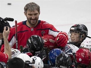 Alexandr Ovečkin se zdraví s čínskými dětmi na tréninku.