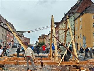 Tesaři na náměstí v Chebu sestavují a vztyčují pomocí bidla a kladkostroje...