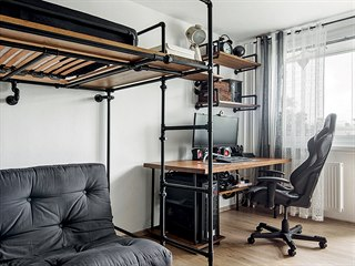 Ve studentském pokoji stojí kovový psací stůl s dřevěnou deskou. Musí být dost...