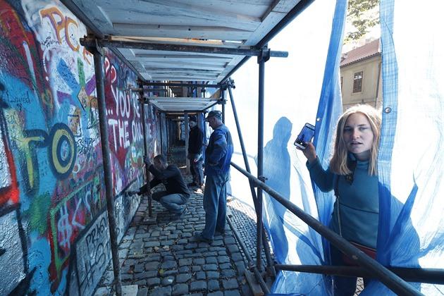 Lennonovu zeď zakryla modrá plachta, pracovníci začali strhávat omítku