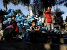 Children fill bottles with water next to a pile of garbage at a makeshift camp...