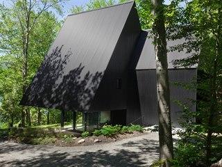 Přesah trojúhelníkové střechy jedné části vytváří krytý vnější prostor vhodný...