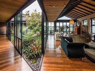 Pohled do chodeb a obývacího pokoje, který má výhled do zeleně ze tří stran.