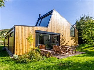 Nevšední geometrii domu zvýrazňuje vertikální modřínová fasáda. Elegantním...