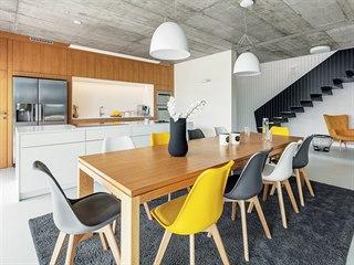 Velký jídelní stůl z dubového dřeva ladí s čelními plochami kuchyňské linky....