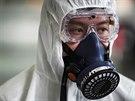 Muž v bezpečnostním obleku se připravuje na dezinfekcí kabiny letadla na...