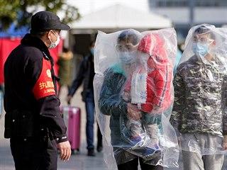 Někteří cestující na vlakové stanici v Šanghaji se kvůli koronaviru chrání...