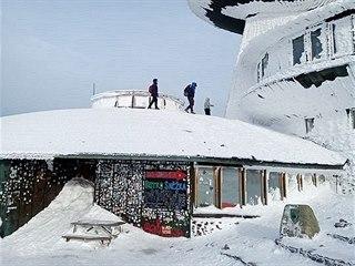 Turisté lezou na střechu meteostanice na Sněžce.