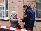 Policista pomáhá ženě zapálit svíčku před šiša barem v německém městě Hanau,...