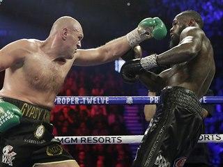 Tyson Fury (vlevo) a Deontay Wilder v boji o pás mistra světa těžké váhy...