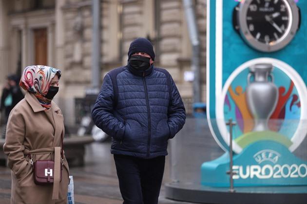 Lidé v ruském Petrohradu zahalení rouškami procházejí kolem poutače na...