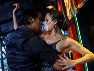 Tanečnice s rouškou a tanečník v gumových rukavicích předvádějí v argentinském...