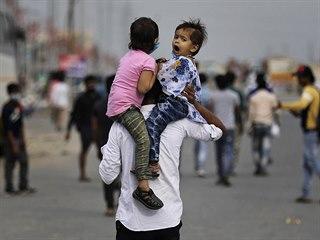 Otec s dětmi na cestě do svého domova. Nespočet obyvatel Indie se v důsledků...