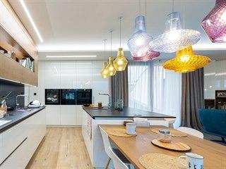 Nad kuchyňským ostrůvkem a jídelním stolem oživují prostor barevně výrazná...