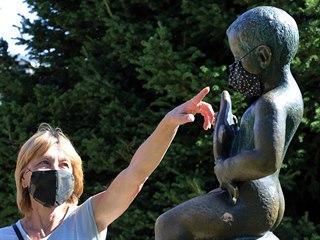 Lázenští hosté u sochy Františka v roušce.