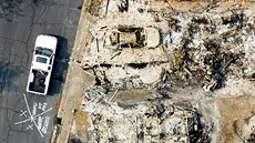 This aerial image taken with a drone, a person searches through the remains of...