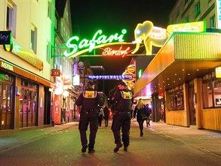 Policisté prochází ulicí v Hamburku. Od 23:00 zde musí mít všechny bary a...