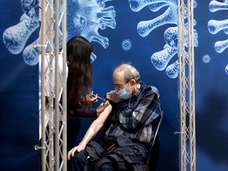 Senior se nechává očkovat proti onemocnění covid-19 ve vakcinačním středisku v...