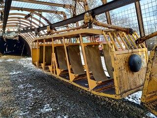 Závěsný vozík na přepravu horníku v podzemí pověšený na závěsné kolejnici.