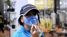 Ženy si malují barvami na obličej falešné roušky