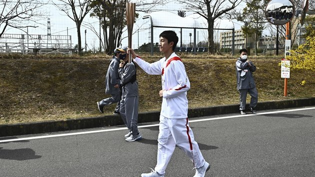Japanese high school student Asato Owada carries an Olympic Torch during the...
