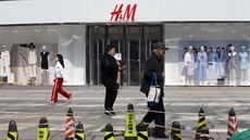 People walk past a store of the Swedish fashion retailer H&M at a shopping...