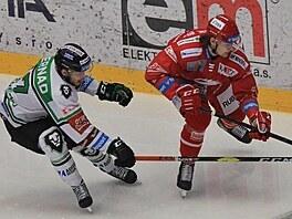 Třinecký Michal Kovařčík se snaží dostak k puku před Davidem Bernadem z Mladé...