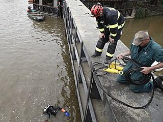 Potápěči spolu s hasiči kvůli povodňové výstraze uzavírají vrata na říčce...