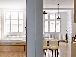 Pohled z chodby do pokojů, kde převažuje nábytek z překližky.