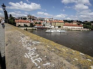 Neznámý vandal posprejoval část Karlova mostu v Praze. Podle policie je nápis u...