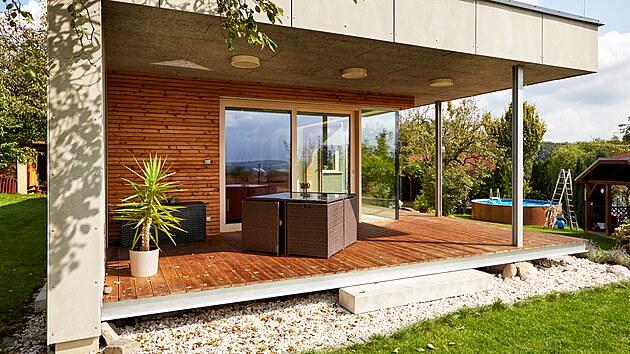 Terasa postavená ze sibiřského modřínu na ocelových válcovaných profilech slouží jako pohodlné závětří a volnočasový prostor. Její strop zachovává jednotu cementotřískového podhledu po vzoru interiéru a má i stejnou výškovou úroveň.