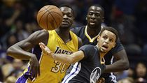 Julius Randle (vlevo) z Lakers v souboji se Stephenem Currym.