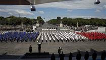 French students stand as they hold placard reading Freedom, equality and brotherhood as they sing the French National anthem attend the Bastille Day military parade on the Champs-Elysees in Paris