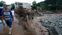 People walk in a destroyed area after heavy rains caused several rivers to...