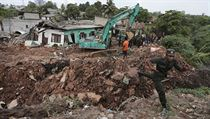 Sri Lankan army soldiers and rescue workers stand near buried houses in a collapse of a garbage dump in Meetotamulla, on the outskirts of Colombo, Sri ...