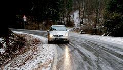 Silnice na horách pokrývá rozbředlý sníh. Viditelnost snižují přeháňky