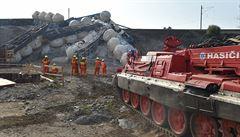 Část vykolejeného vlaku s vápnem se podařilo během noci odstranit z trati. Hasiči se snaží vagony i rozřezat