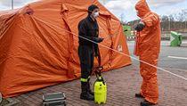 Příslušník polské pohraniční policie dezinfikuje kolegu vochranném oděvu...
