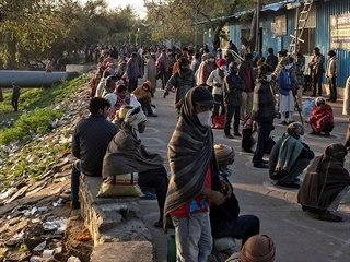 Bezdomovci stojí frontu na jídlo v indickém Novém Dillí.