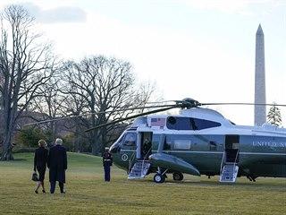 Prezident Donald Trump s manželkou kráčí k helikoptéře.