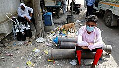 FILE PHOTO: Sumit Kumar, 28, sits on an oxygen cylinder as he waits outside a...